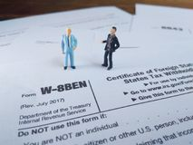 Two businessman discussion about usa tax form, w-8ben, certificate of foreign status of beneficial owner for united states tax wit. Photo two businessman stock photography