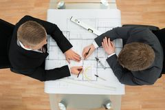 Two businessman drawing plan on blueprint Royalty Free Stock Images