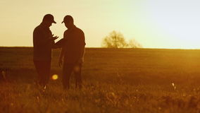 Two businessman farmers shake hands with each other firmly. They talk on the field against a beautiful sunset, they use