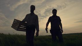 Two businessman farmers shake hands with each other firmly. They talk on the field against a beautiful sunset, they use stock footage