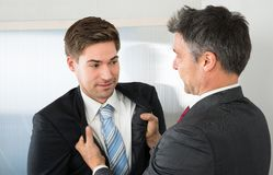Two businessman fighting. Angry Mature Businessman Holding Coat Of Young Businessman Stock Photography