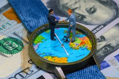 Two businessman figurines on time and money background. Worldwide business concept. International business agreement. Global corporation strategic partnership stock photo