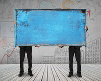 Two businessman hold old blue blank wooden noticeboard stand Stock Photo
