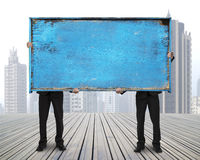 Two businessman hold old blue empty wooden noticeboard Royalty Free Stock Photography