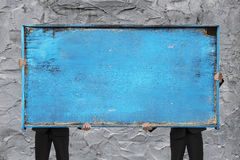 Two businessman holding old blue empty wooden noticeboard Royalty Free Stock Photos
