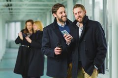 Two businessman holding smart phone in lobby with colleagues at background Stock Images