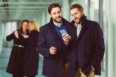 Two businessman holding smart phone in lobby with colleagues at background.  Royalty Free Stock Photos