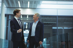 Two businessman interacting with each other in corridor. At office Stock Photography