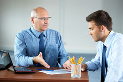 Two businessman with laptop discuss something Royalty Free Stock Images
