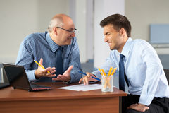 Two businessman with laptop, office as background Stock Images