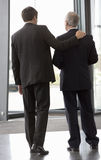 Two businessman leaving an office building Stock Photos