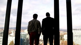 Two businessman looking on city through window. Back view of two businessman looking on city through window stock video