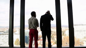 Two businessman looking on city through window and talking. Back view of two businessman looking on city through window and talking stock footage