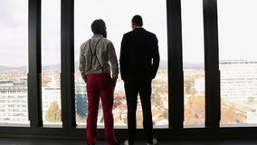 Two businessman looking on city through window and talking. Back view of two businessman looking on city through window and talking stock video footage