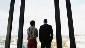 Two businessman looking on city through window and talking stock video footage
