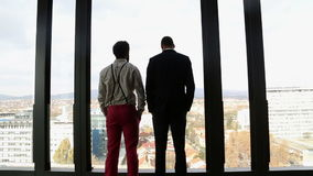 Two businessman looking on city through window and talking stock footage