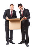 Two Businessman looking inside a box and smiling Stock Photography