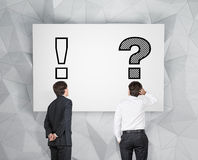 Two businessman. Looking at question and exclamation mark Royalty Free Stock Photo