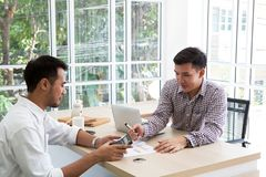 Two businessman plaining data at meeting. Business people meeting around desk. asian people. brainstorming of business. royalty free stock photo