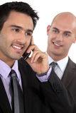 Two businessman receiving a call. Two businessmen receiving good news over the phone Stock Photo