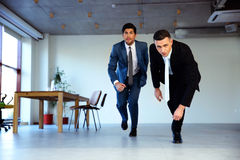 Two businessman running together. In office. Business concept Royalty Free Stock Photography