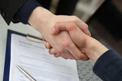 Two businessman shake hands as hello in office closeup Royalty Free Stock Image