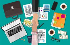 Two businessman shake hands. After the signed contract. Contract agreement. Desktop laptop, calculator, contract financial papers, coffee, pen, notes, briefcase Royalty Free Stock Images