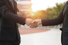 Two businessman shaking hand to negotiate businessman. Outside stock images