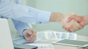 Two businessman shaking hands greeting each other. Two successful businessman sitting at the negotiating table in the office and shake hands with each other stock footage