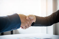 Two businessman shaking hands during a meeting in the office, su Royalty Free Stock Photo