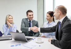 Two businessman shaking hands in office Stock Images