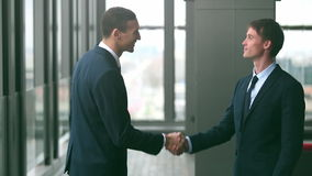 Two businessman shaking hands. Profile of two businessman shaking hands, graded stock footage