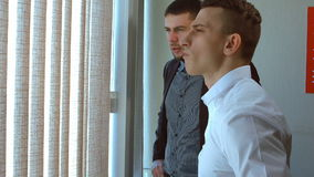 Two businessman talking by the window stock video footage