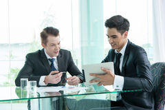 Two businessman using tablet during meeting Stock Photo
