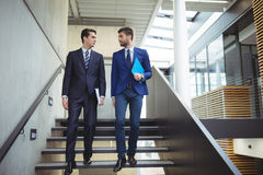 Two businessman walking downstairs stock photos