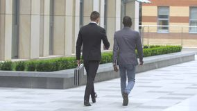 Two businessman walking on the street near office building. African American businessmen and European businessman,walking through crowded high building street stock video footage