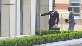 Two businessman walking on the street near office building. slow motion. African American businessmen and European businessman,walking through crowded high stock video