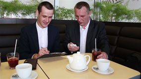 Two businessman writes data from smartphone in a documents. Two businessman sitting in a cafe and writes data from smartphone in a documents stock video footage