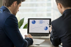 Two businessmen analyzing stats on laptop, accounting software,. Rear view at two businessmen analyzing stats financial data on pc laptop, pointing at screen Royalty Free Stock Photos