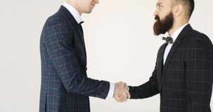 Two businessmen approach each other and shake hands. Handshake: two businessmen shaking hands stock video footage