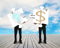 Two businessmen assembling puzzles for Idea is Money doodles Stock Image