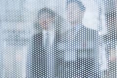 Two businessmen behind a glass wall looking out, unrecognizable faces Stock Photography