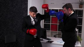 Two Businessmen Boss and his empoyee Boxing in Office Room. Two Young handsome attractive Businessmen Boss and employee Boxing in Office Room. Red and blue stock video footage