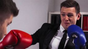 Two businessmen boxing in office room. Two attractive businessmen boxing in office room. Red and blue gloves. Super slow motion shot. Competition and fighting in stock video