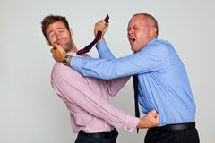 Two businessmen brawling. Photo of two businessmen fighting each other, part of a series see my portfolio for them shaking hands and hugging Stock Photo
