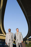 Two businessmen with briefcases beneath overpasses, low angle view Stock Image