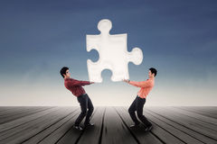 Two businessmen bring puzzle outdoor Stock Images