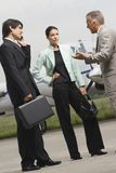 Two businessmen and a businesswoman standing at an airport Royalty Free Stock Photo