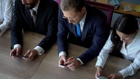 Two Businessmen and Businesswomen surfing the mobile phone while sitting on the table in the office. The women are wearing white blouses. Men are wearing black stock footage