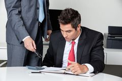 Two Businessmen Calculating Finances Stock Image